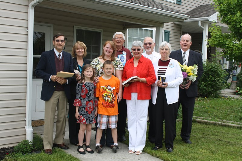 Dedication Day: Biglerville resident Amy Sefcheck and children Vincent, 9, and Abigail, 7, are surrounded by Adams County Habitat for Humanity board members and spouses Sunday during a formal dedication and blessing of the home.