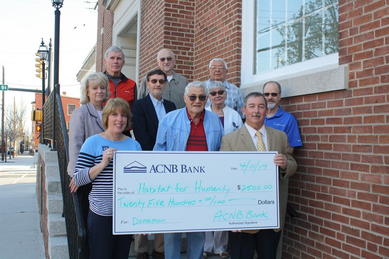 ACNB Bank Donation Benefits Adams County Habitat for Humanity: Front: Lauren Muzzy of ACNB Bank, with Habitat Board Members Bill Scott, Pete Ricker. Middle: Sue Pindle, Lynn Cairns, Judy Leslie, Bob Boehner. Back: Bill Tyson, Bill Leslie, John Phillips.